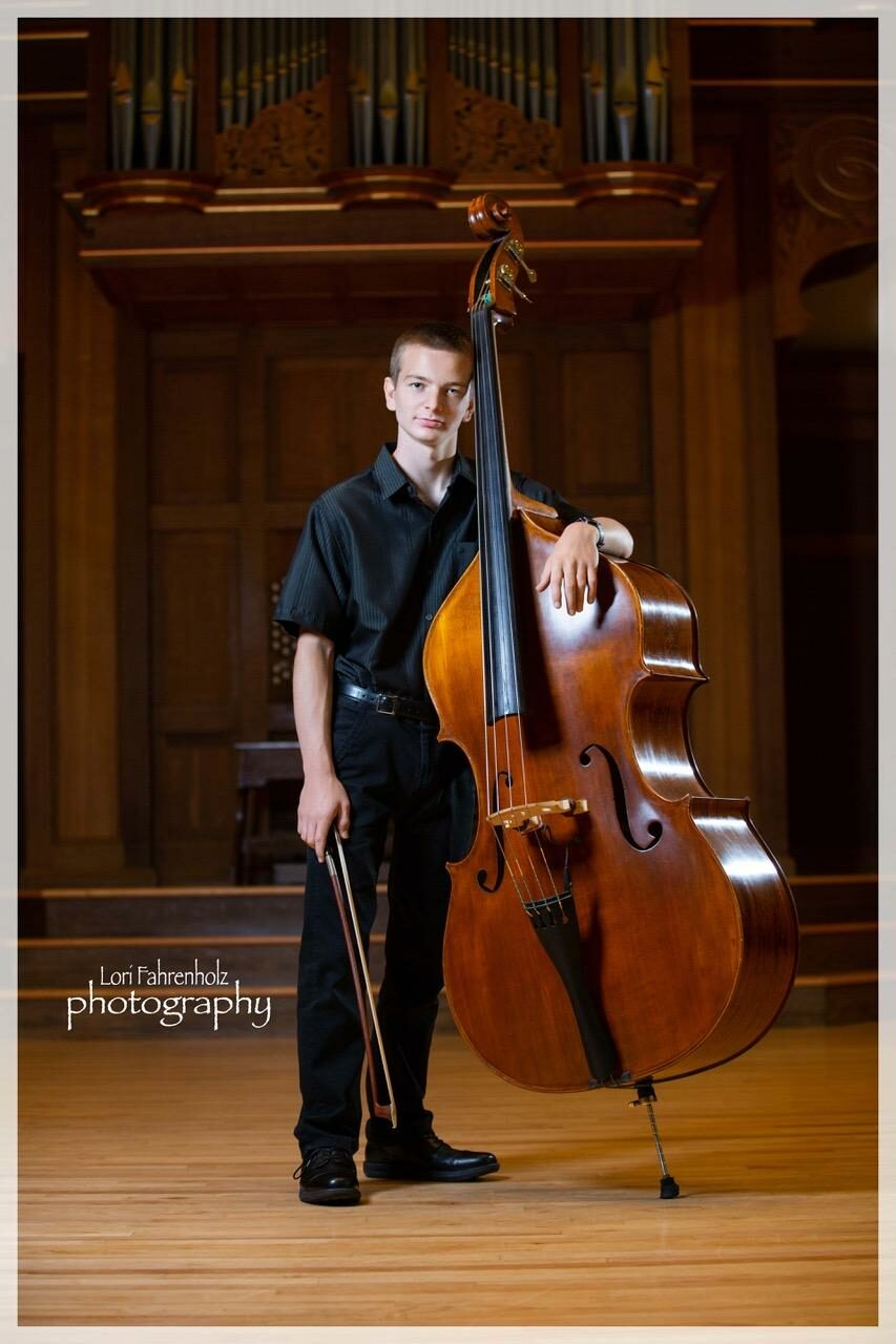 A student wearing concert black stands on the Lawrence Chapel stage in concert black. He holds a string bass and bow and smiles at the camera.