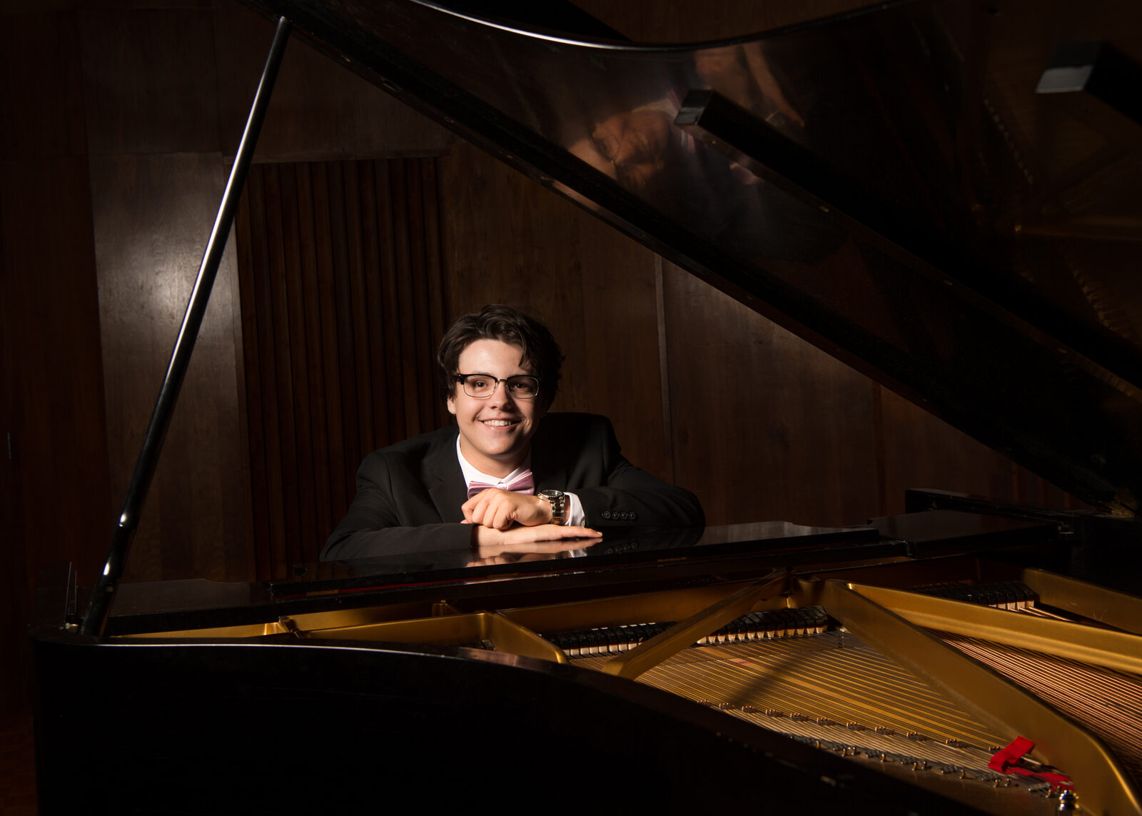 A student wearing glasses and a suit sits at a grand piano, smiling and leaning over the instrument with his hands crossed.