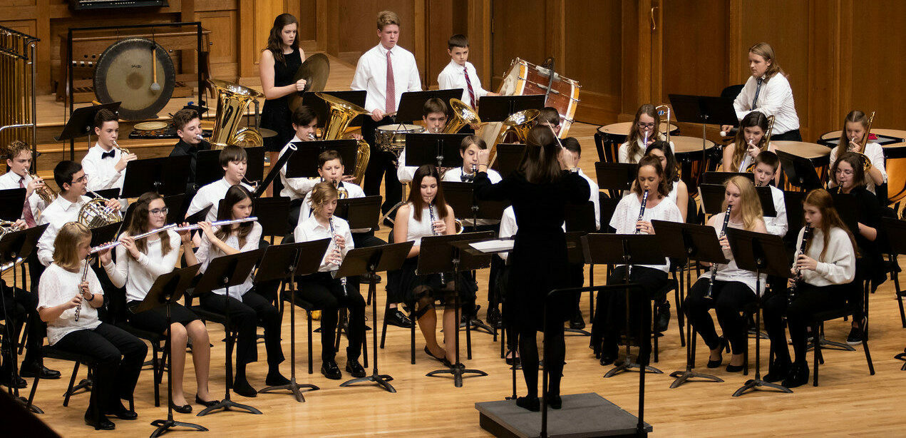 Symphonic Band performing onstage during a concert. Their conductor stands in front with her arms raised.