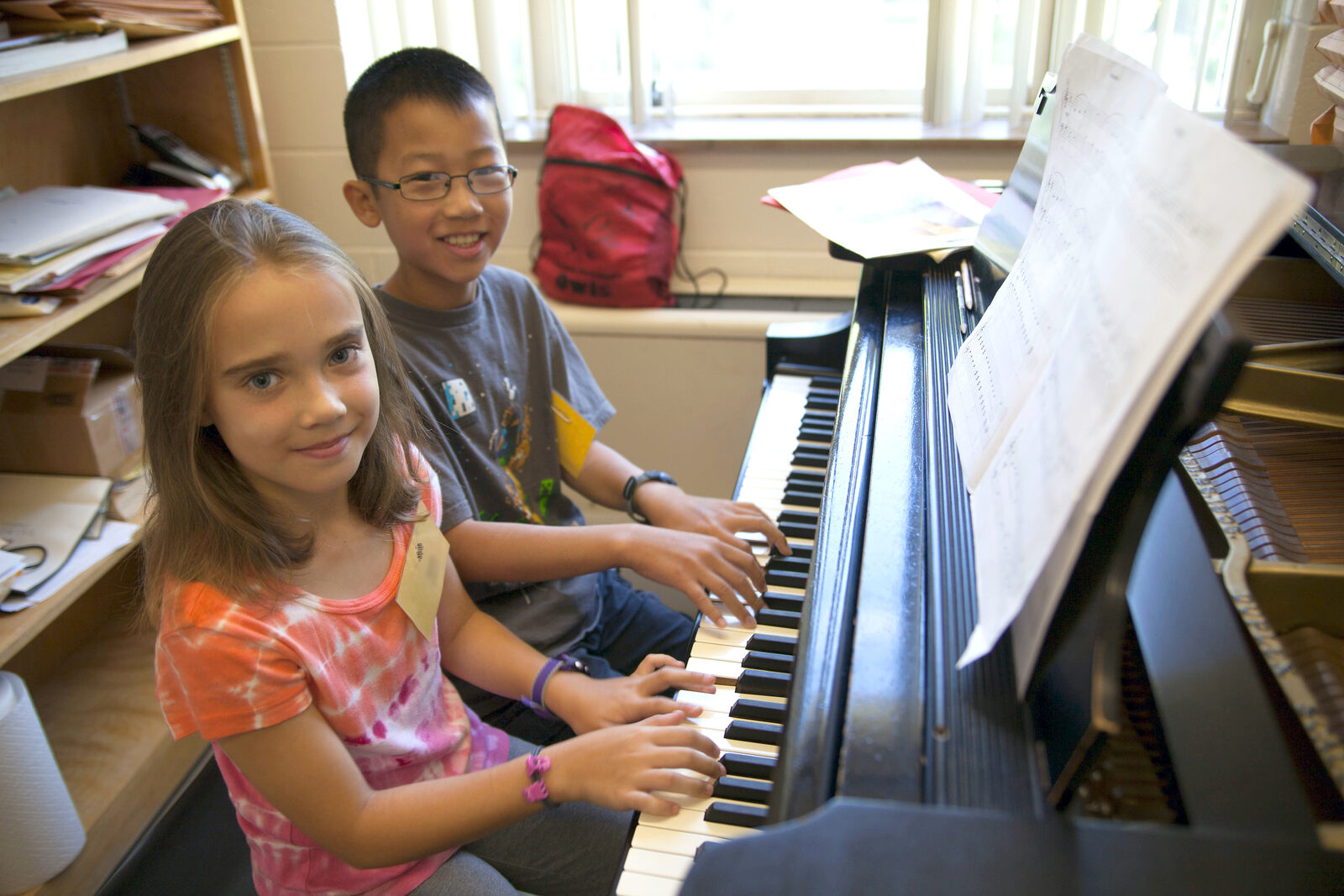 A young boy and girl sit at a piano in a studio. Both have their hands on the keys and smile at the camera.