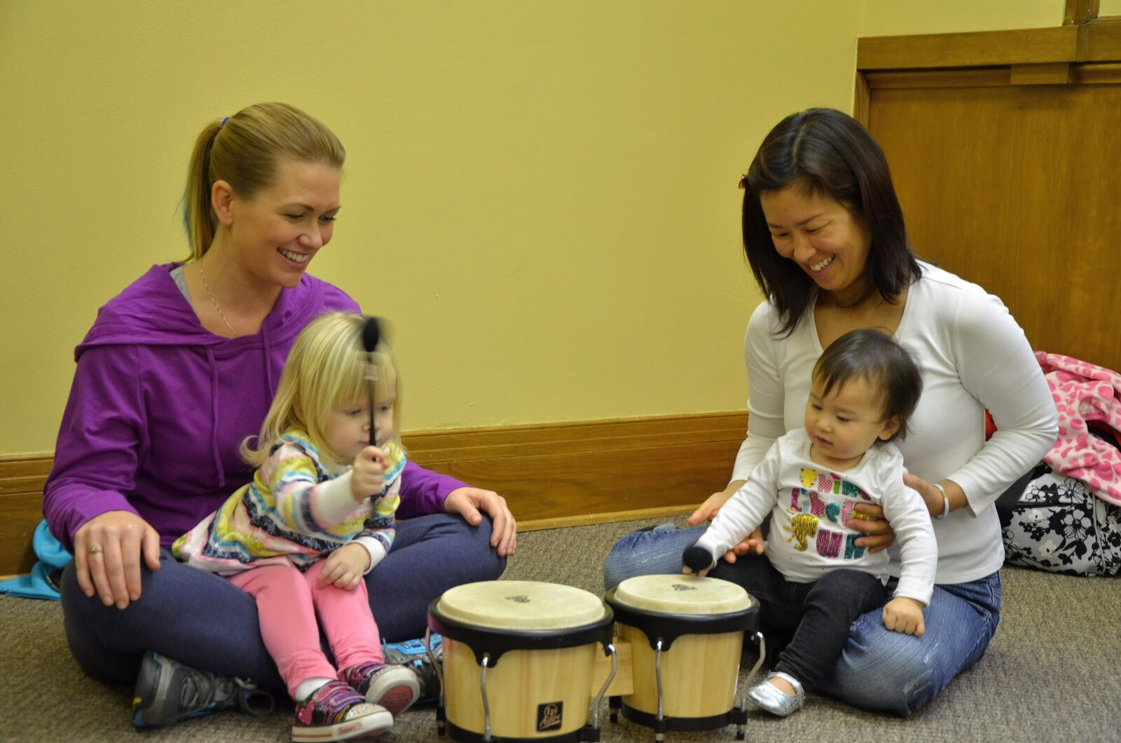 Two smiling mothers are holding their toddlers on their laps, the children are holding mallets and playing a drum