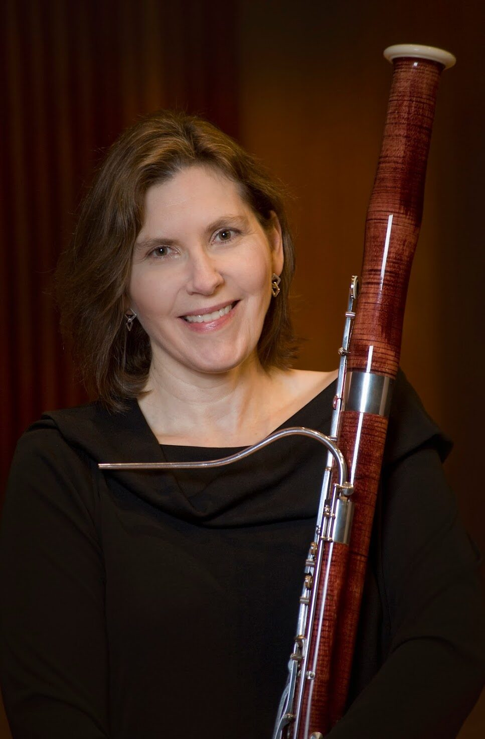 A woman with shoulder-length, wavy hair holds a bassoon and smiles at the camera.