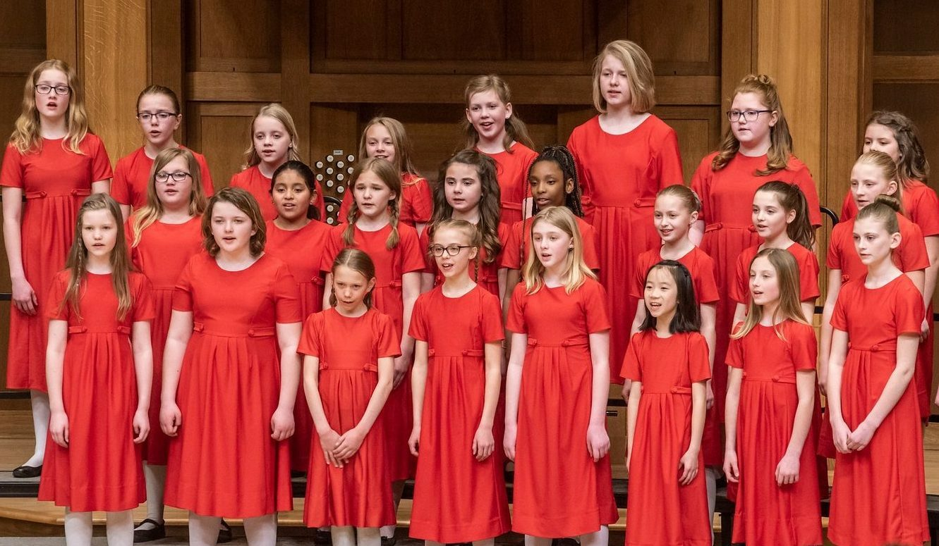 Allegretto students singing on stage. They wear red, short-sleeved dresses and white tights.