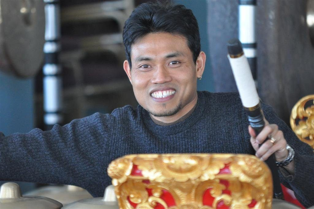 smiling gamelan teacher with red and gold instrument