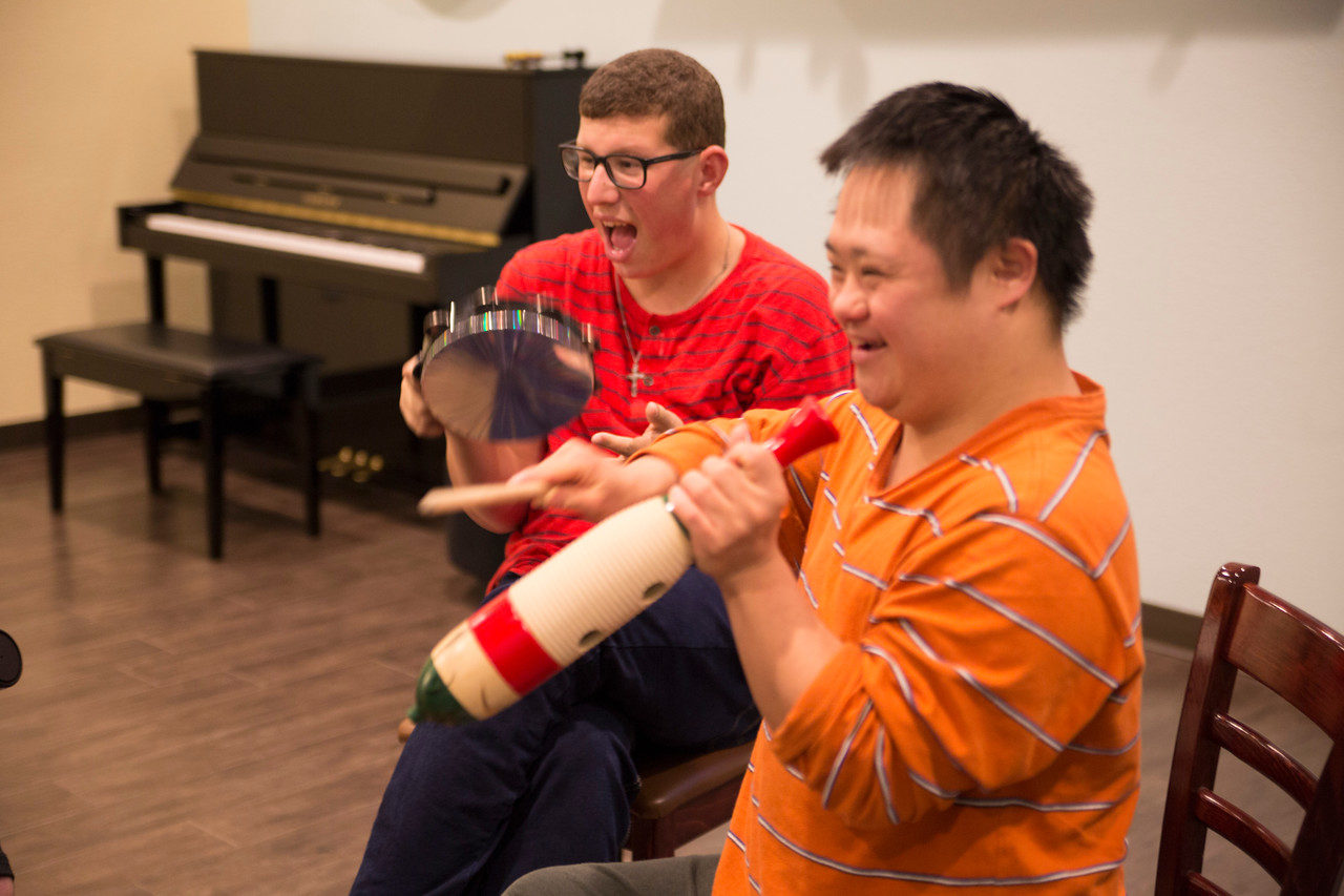 A student in an orange striped shirt playing a guiro and a student in a red striped shirt playing the tambourine.