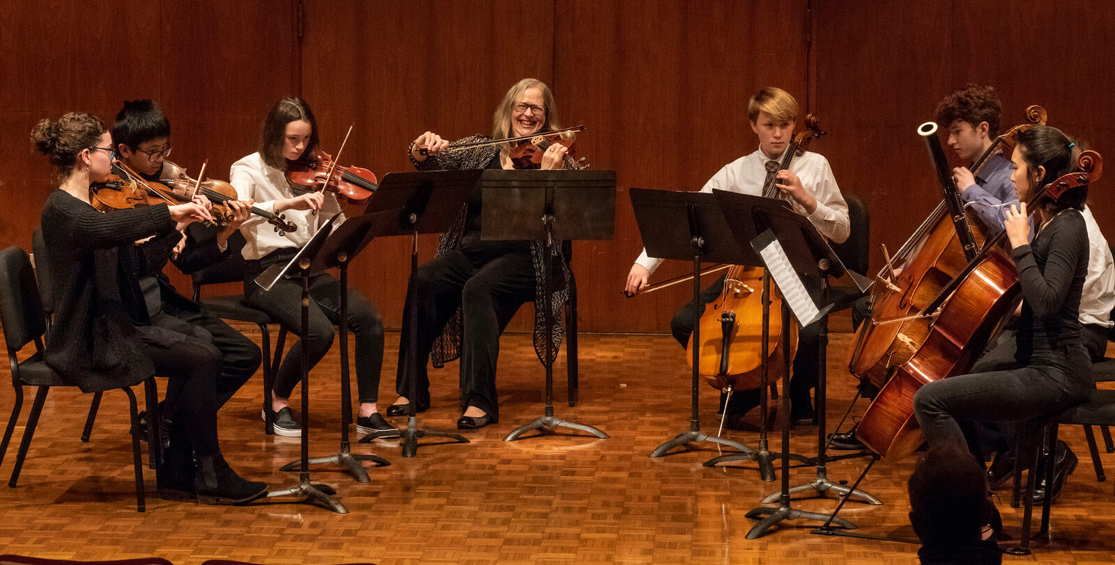 Chamber ensemble students and their instructor perform onstage during a recital. They play a variety of string and wind instruments.