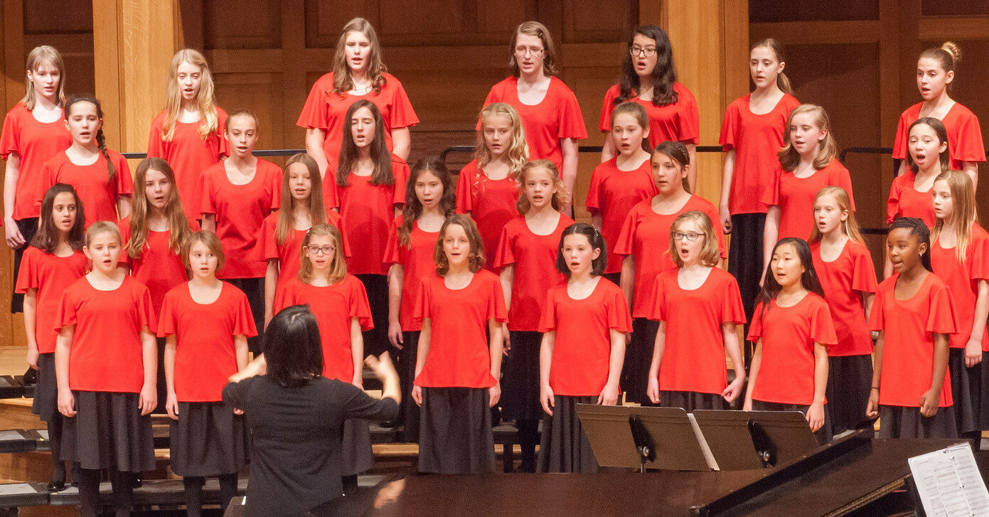 Capriccio students singing onstage during a concert. They wear red, short-sleeved blouses and black, knee-length skirts with black pantyhose.