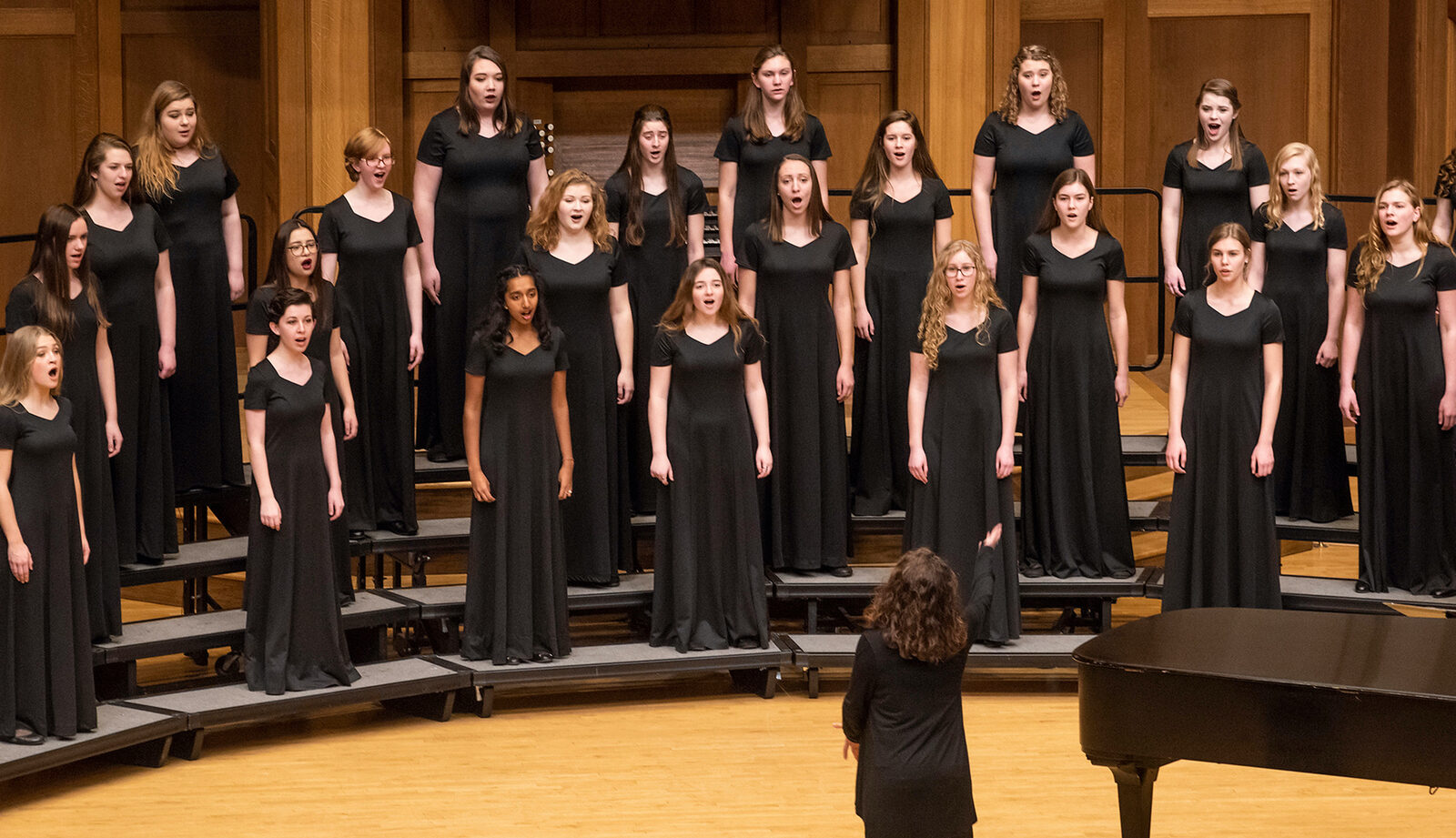Bel Canto performing during a concert. They wear floor-length, short-sleeved, black dresses.