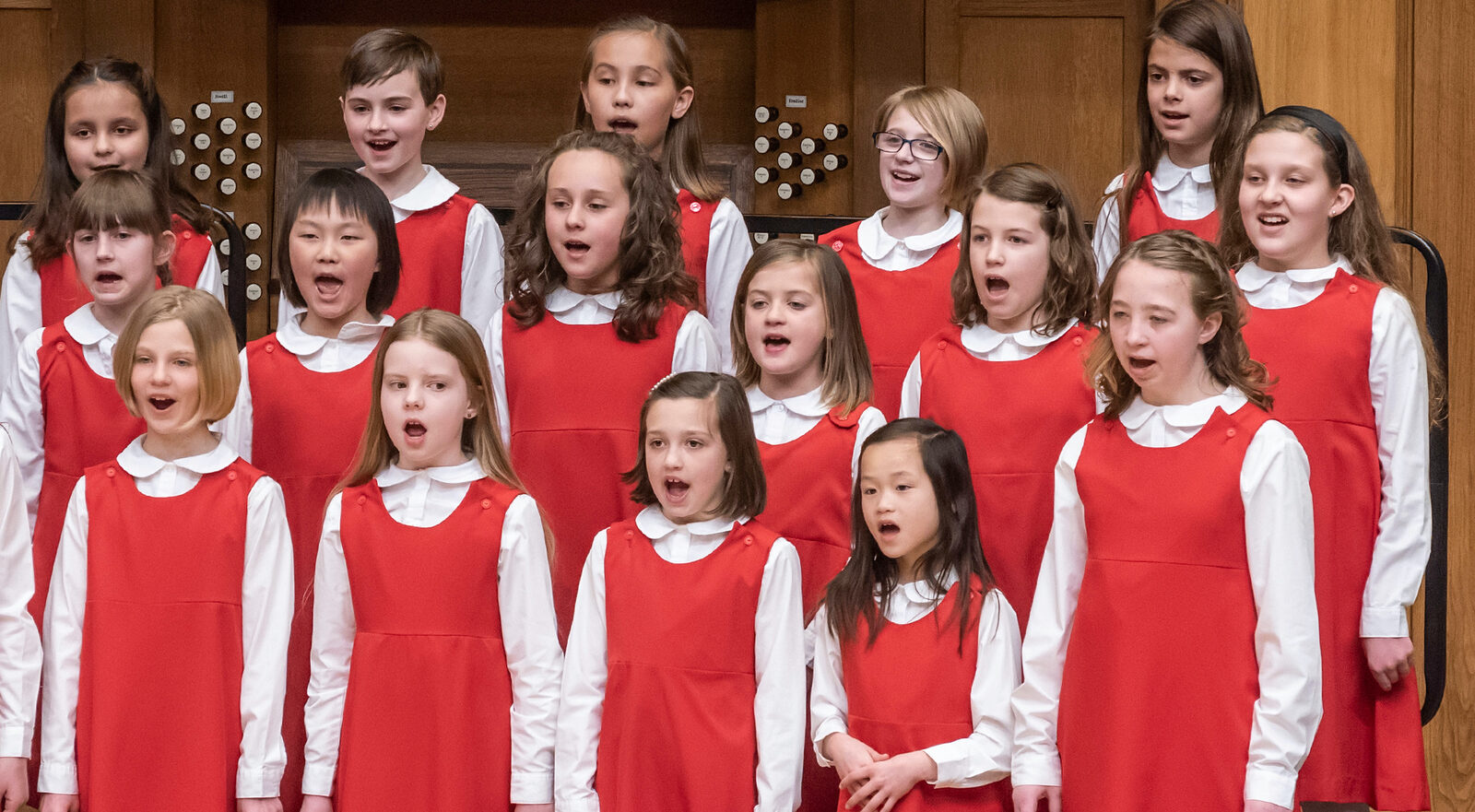 The Primo Girl Choir singing in the Chapel. They're wearing red jumpers with white tights and white, long-sleeved shirts with Peter Pan collars.