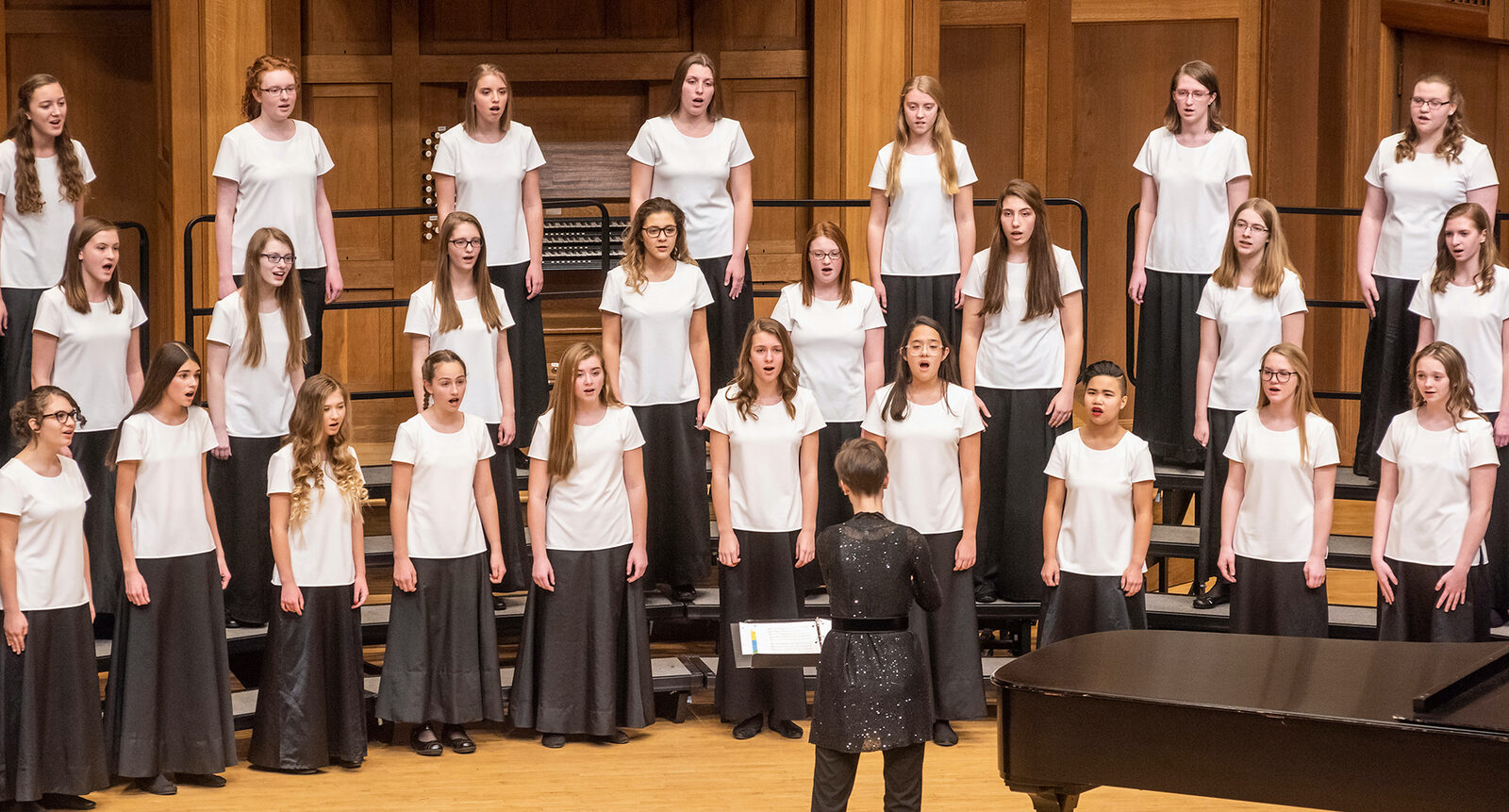 Cantabile singing onstage during a concert. They wear white, short-sleeved blouses and long black skirts or black pants. Their conductor stands in front of them.
