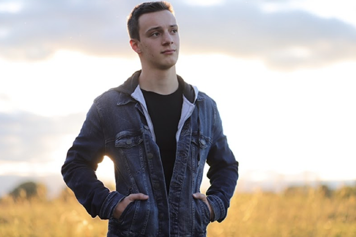 A student stands in a field with his hands in his jacket pocket. He stares into the distance with a slight smile on his face.