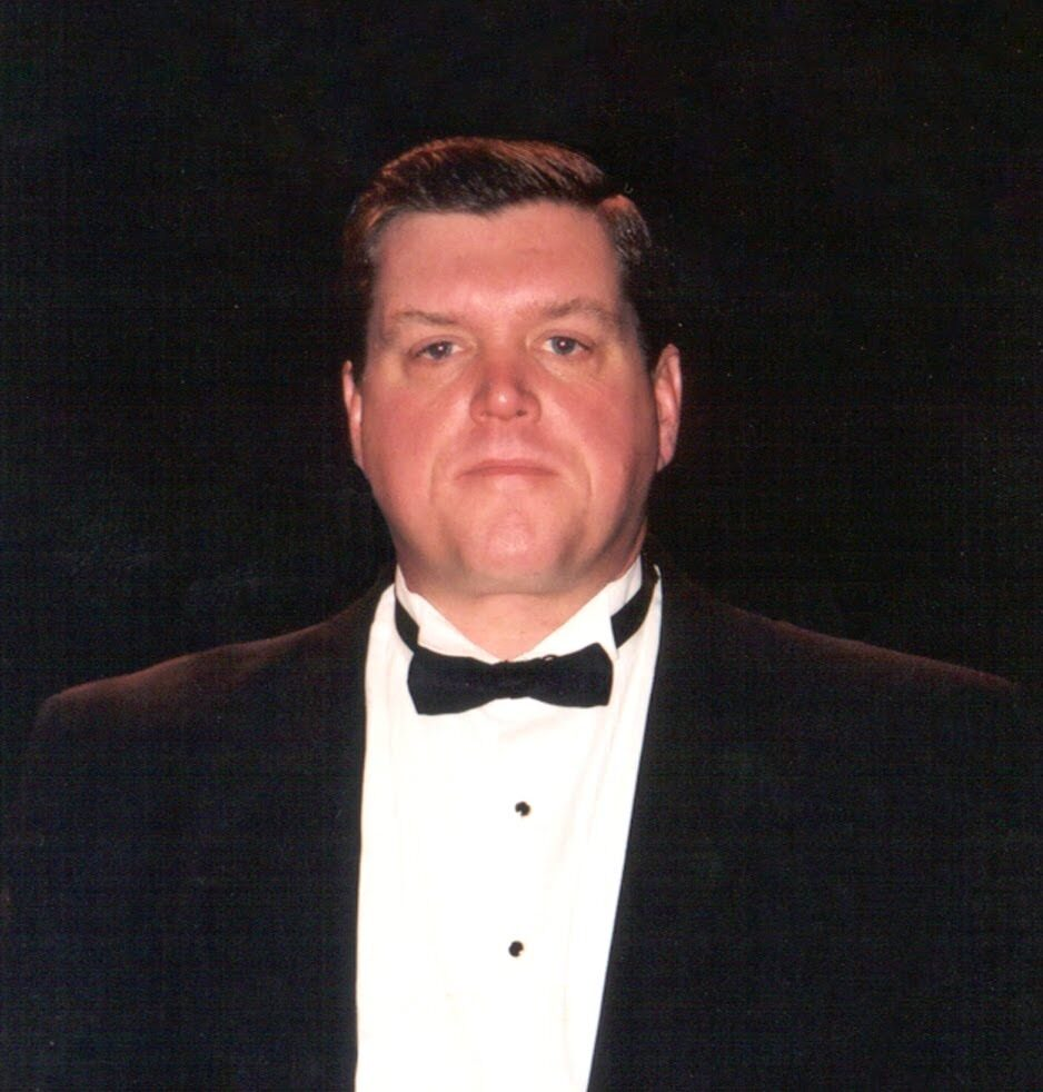A closeup of a man in a tuxedo looking at the camera. He has a hint of a smile on his face.