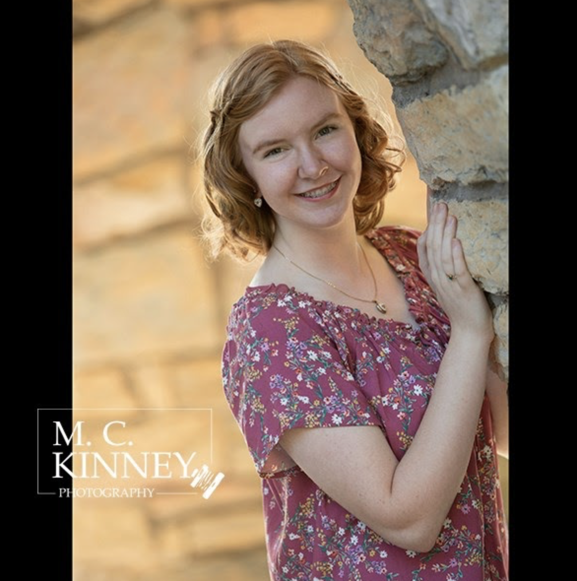 A student with curly, strawberry blonde hair leans against a stone wall and smiles. The photo has a watermark from M.C. Kinney Photography.
