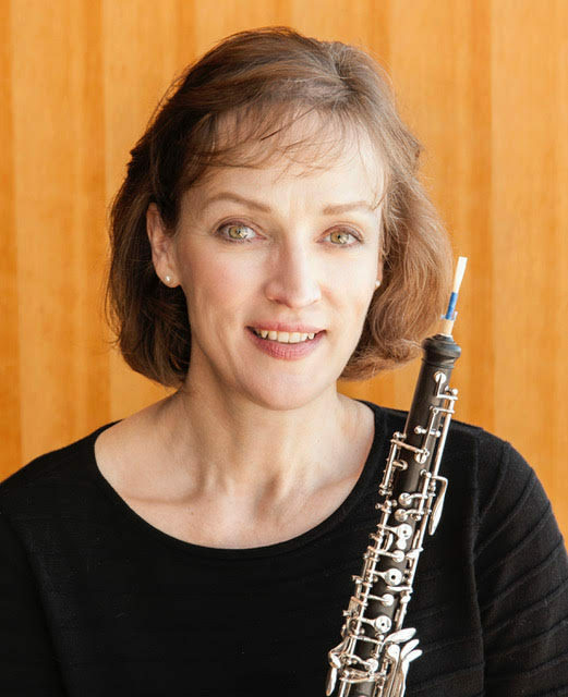 A headshot of a smiling woman with wavy brown hair. She holds an oboe and stands in front of a woodgrain backdrop.