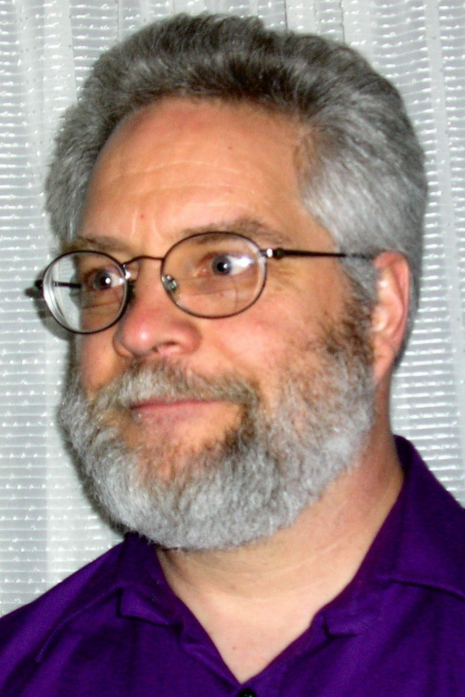 A headshot of a bespectacled man with gray hair and a gray beard.